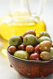 Mixed marinated olives (green, black and purple) in ceramic bowl  and olive oil