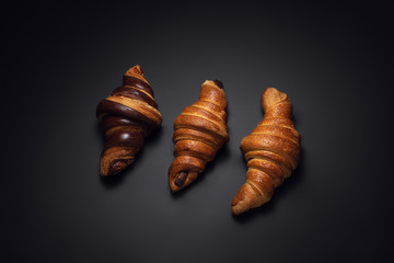 French croissants with chocolate on black background. Top view.