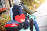 Beautiful young couple holding hearts while riding scooter in city in autumn