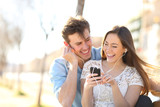 Joyful couple listening to music from a smartphone in a pak - 231751992
