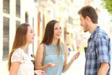 Three smiley friends talking in the street - 231751993