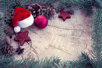 Christmas hat with bauble and fir branches on wood background.Christmas card.