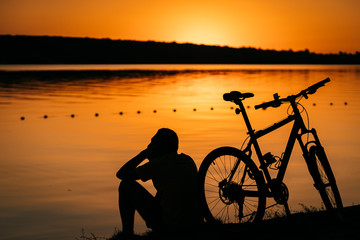 The guy rests on the river bank. © teksomolika