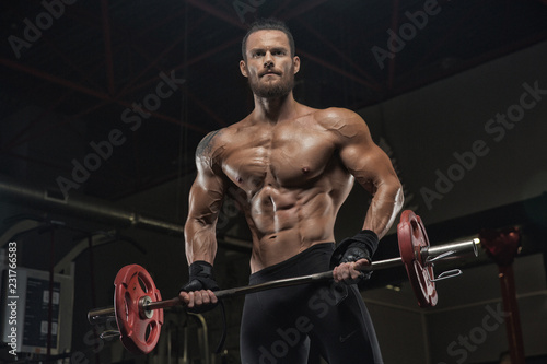 Wall mural Young handsome athlete bodybuilder, weightlifter, doing crossfit, with a sledgehammer, in a modern gym. Concept-strength, beauty, power, sport, health, sports nutrition, diet, styroydy, scales.