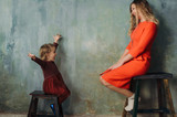 Young woman and little girl in same dresses having fun - 231771967