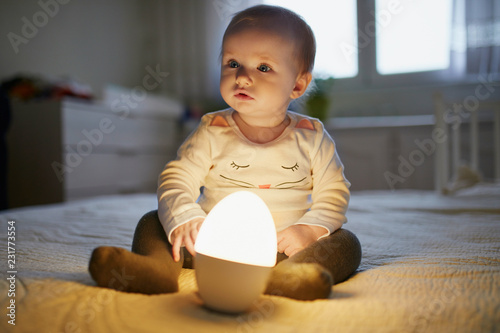 Leinwanddruck Bild Adorable baby girl playing with bedside lamp in nursery