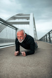 Active senior man doing plank exercise outdoors in the city. - 231781728