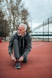 Handsome senior in sportswear preparing for a run. - 231782142