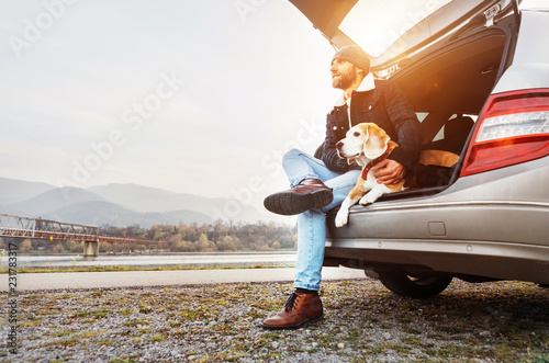 Leinwanddruck Bild Breaded man in warm clothes siting with beagle in car trunk. Traveling with pet