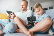 Quadro Father and son, PC gamers, enthusiastically playing with electronic devices: tablet and gamepad