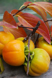 persimmons with leaves and stems, vertical close up - 231785345