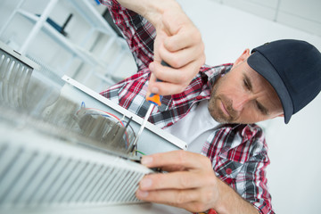 Man using screwdriver on electric heater