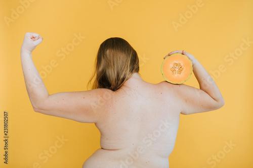 Leinwandbild Motiv Strong blond woman holding a cantaloupe melon