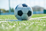 Extreme close up of football ball lying on grass in outdoor field, copy space - 231803730