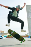 Full length portrait of contemporary young man doing skateboard stunts outdoors in extreme park © seventyfour