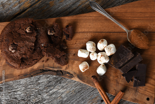 Overhead view of a cutting board with chocolate chunks cinnamon sticks and cookies