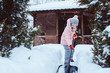 kid girl helping to clean pathway from snow with showel. Child playing in snowy winter garden