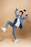 Full length image of man which listening to music and jumping in studio. Vertical image - 231828599
