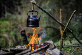 Old teapot boils on campfire