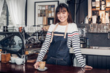 Asian female barista wear jean apron place her hand on counter bar and smiling to customer,cafe service concept,owner business start up - 231830756