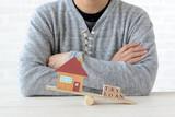 住宅と支払いのバランスを考える男性