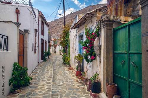 beautiful view of scenic narrow alley with  traditional houses colorful flowers and cobbled street  in a village of crete.