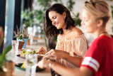 food and people concept - female friends eating at restaurant or cafe - 231833128