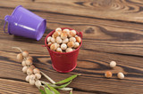 Full metal red bucket of raw olives and olives on twig with green leaves near empty violet bucket on old rustic wooden table with copy space for your text