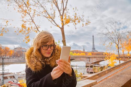 Leinwanddruck Bild Girl using cellphone with Paris city background and Eiffel tower.