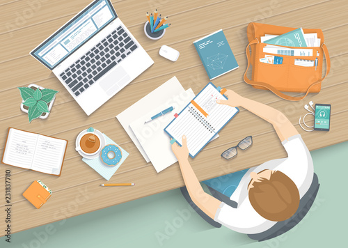 Man sitting at the wooden table. Workplace Desktop Workspace Armchair, office supplies, monitor, books, notebook, headphones, phone, glasses, pen, bag, tea, donut. Vector Top view