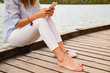 Leinwanddruck Bild - Girl on a wooden pier using smartphone.
