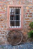 Holzrad lehnt an einer Mauer - 231853729