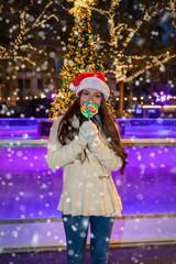 Junge, attraktive Frau mit einer Weihnachtsmütze auf einem Weihnachtsmarkt hält einen bunten Lolli in der Hand
