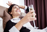 Being rich. Happy young maid drinking champagne while dreaming of better life - 231871956