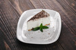 White cheesecake with cacao topping and mint served on a white plate.