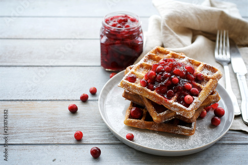 Poster Belgian waffles  with cranberry sauce for breakfast. Light wooden background