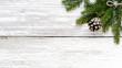 Leinwanddruck Bild - Fir branch and pine cone on white wood plank