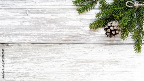 Leinwanddruck Bild Fir branch and pine cone on white wood plank