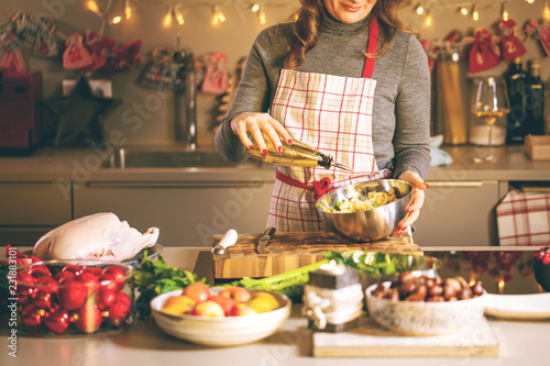 Foto Murales Young Woman Cooking in the kitchen. Healthy Food for Christmas (stuffed duck or Goose)