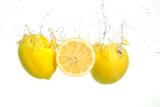 Three lemons spash in water on white