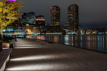 Night photo of the Boston waterfront with views over the bay and luminous skyscrapers. USA. Masachuses.