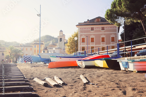 Beautiful beach with yellow sand and colorful boats in old Italian town Sestri Levante (Liguria) on sunset.