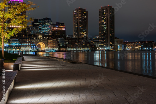 Poster Night photo of the Boston waterfront with views over the bay and luminous skyscrapers. USA. Masachuses.
