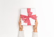 Person holding a Christmas gift box on a white background