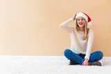 Happy woman with a Santa hat on a white carpet