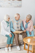 senior cheerful people sitting on sofa and reading book together