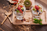 Two glasses of delicious yogurt and fruits ion wooden table