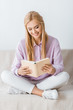 beautiful smiling woman reading book and sitting on sofa