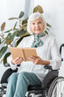 happy senior woman sitting in wheelchair and reading book