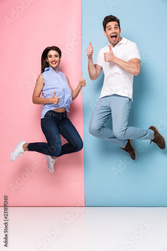 Leinwanddruck Bild Full length image of cheerful man and woman in casual wear jumping and smiling together, isolated over colorful background